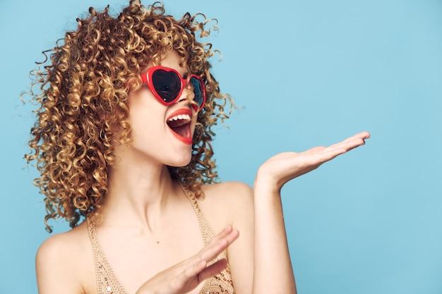 Glückliche mädchenhandgesten auf einer isolierten blauen, roten sonnenbrille und liebe