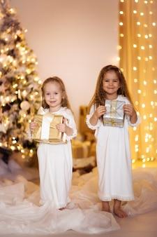 Glückliche mädchenschwesterfreunde kleiden weißgoldhintergrund mit weihnachtsgeschenken