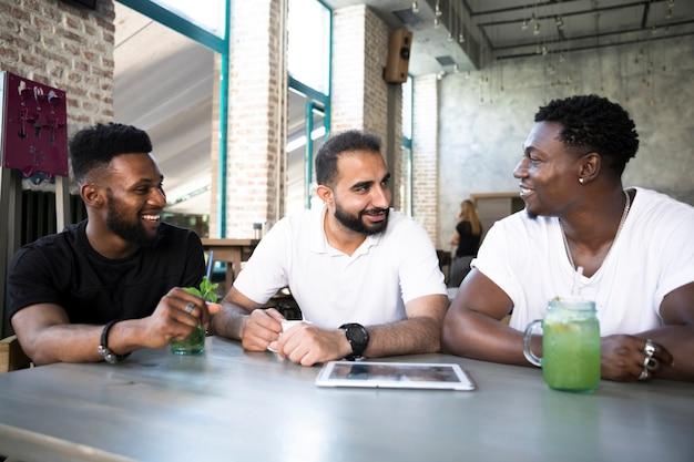 Glückliche männer, die am tisch sich besprechen