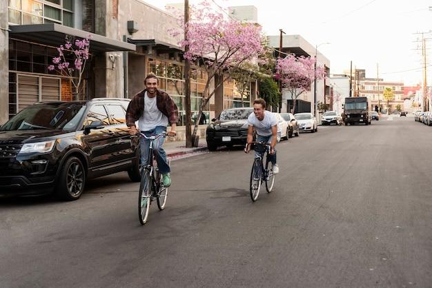 Glückliche männer, die fahrräder in der stadt reiten