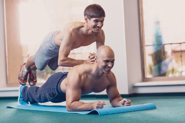 Glückliche männer führen schwierige körperliche übungen durch.