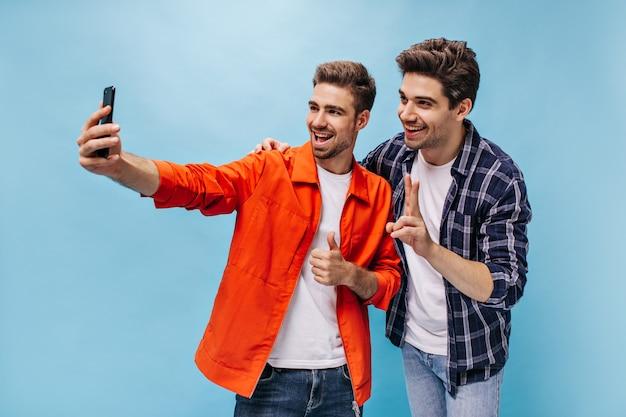 Glückliche männer machen selfie an der blauen wand. der bärtige kerl in der orangefarbenen jacke hält das telefon und zeigt den daumen nach oben. mann im karierten hemd lächelt und zeigt friedenszeichen.