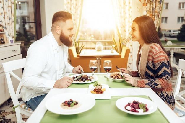 Glückliche männer und frauen des romantischen abendessens im restaurant