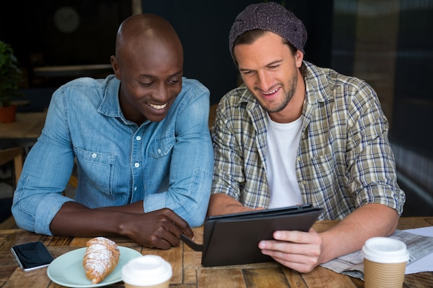 Glückliche männliche freunde, die digitales tablett am tisch im kaffeehaus verwenden