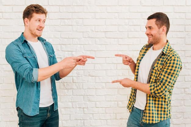 Glückliche männliche freunde, die gegen die weiße wand zeigt ihre finger auf einander stehen