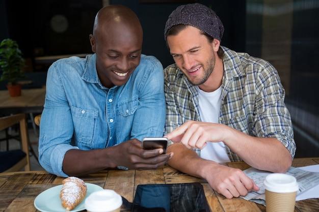 Glückliche männliche freunde, die handy am tisch im kaffeehaus verwenden