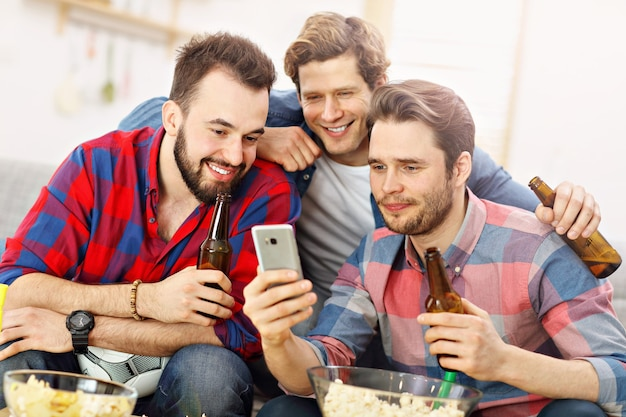 Glückliche männliche freunde, die im fernsehen jubeln und sport gucken