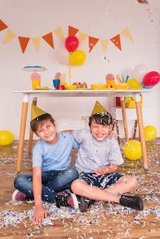 Glückliche männliche freunde, die mit konfetti während der geburtstagsfeier spielen