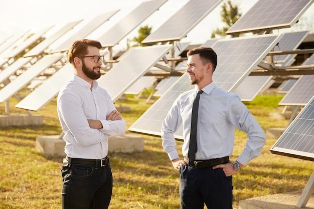Glückliche männliche geschäftspartner diskutieren energieentwicklungsprojekt, während sie in der nähe von photovoltaikmodulen auf grünem solarpark stehen