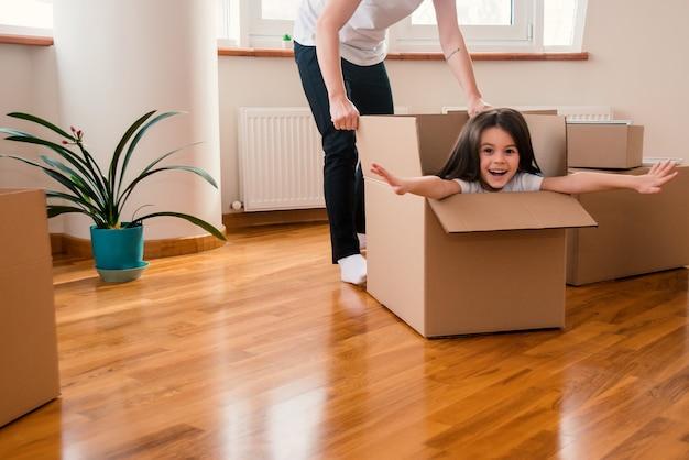 Glückliche mama mit tochter oder kind ziehen im haus um und haben spaß beim auspacken alles in kisten