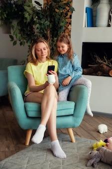 Glückliche mama sitzt mit ihrer tochter auf einem stuhl und schaut sich etwas lustiges am telefon an