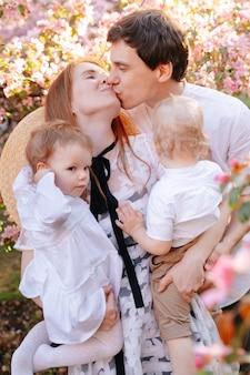Glückliche mama und papa küssen sich und halten zwei kinder, tochter und sohn in ihren armen aus rosenholz in blumenfamilienwerten