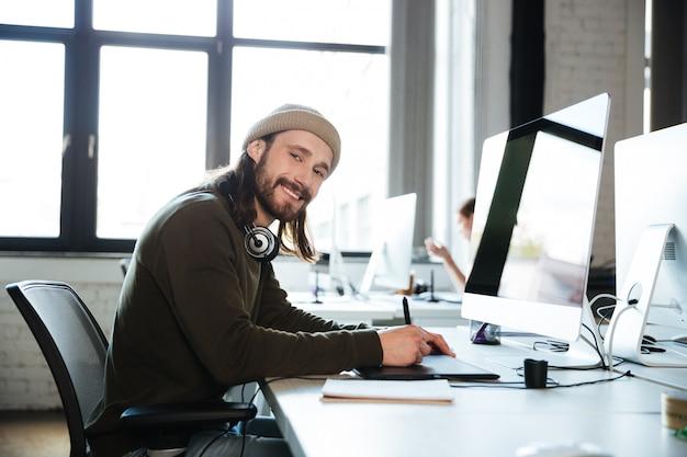 Glückliche mannarbeit, die im büro mit computer aufwirft.