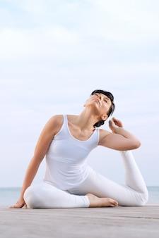 Glückliche meditierende frau, die yoga macht, wirft draußen auf see auf