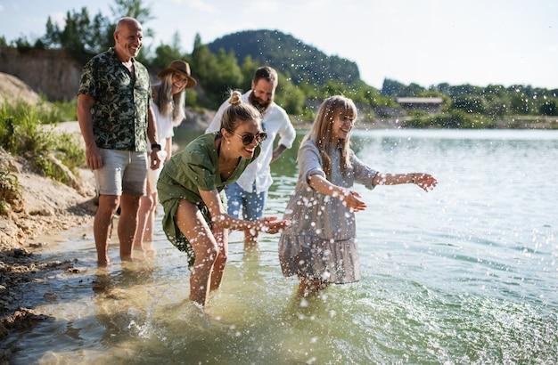 Glückliche mehrgenerationenfamilie auf einem spaziergang am see im sommerurlaub, spaß im wasser.