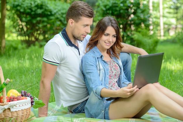 Glückliche menschen auf picknick mit dem laptop im park