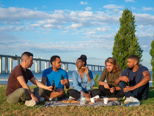 Glückliche menschen, die bier während des sommerpicknicks sprechen und trinken. gute freunde reden und trinken bier. konzept des picknicks