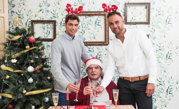 Glückliche menschen, die gläser champagner nahe festlicher tabelle klopfen