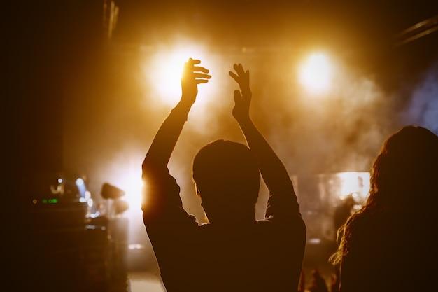 Glückliche menschen genießen rockkonzert, erhobene hände und klatschen vor vergnügen, aktives nachtleben konzept.