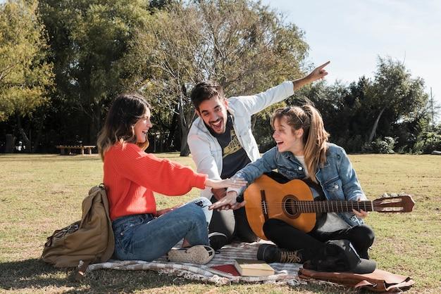 Glückliche menschen mit gitarre auf bettdecke