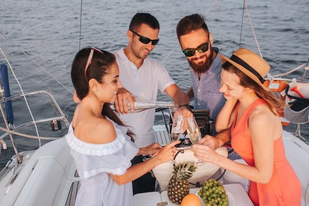 Glückliche menschen stehen zusammen. mann gießt champagner in gläser. frauen schauen nach unten und lächeln. männer tragen eine brille.