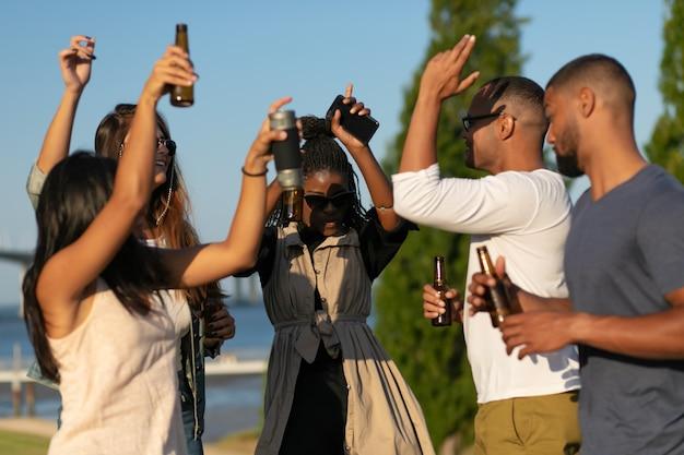 Glückliche menschen tanzen mit bierflaschen