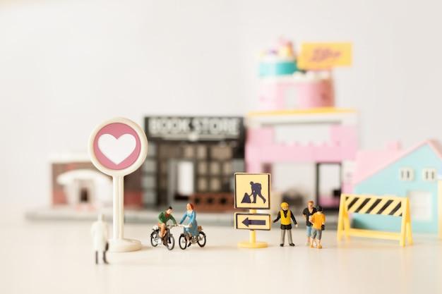 Glückliche miniatur der jungen paare auf fahrradfahrt (miniatur) auf fahrradfahrt in der stadt valentinstag mit selektivem fokus und weicher pastellfarbe getont.