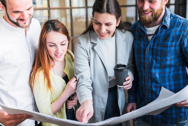Glückliche mitarbeiter, die an blaupause im büro arbeiten