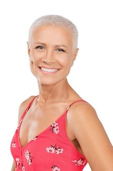 Glückliche mittlere greisin im sommerkleid mit dem lächeln der weißen zähne lokalisiert auf weiß