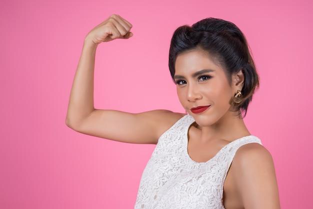 Glückliche modefrau, die ihr muskel gutes gesundes zeigt