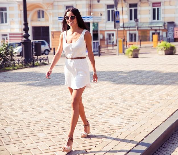 Glückliche modefrau, die in der stadt geht
