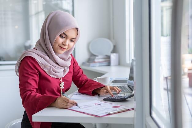 Glückliche moderne asiatische moslemische geschäftsfrau, die an schreibtisch arbeitet.