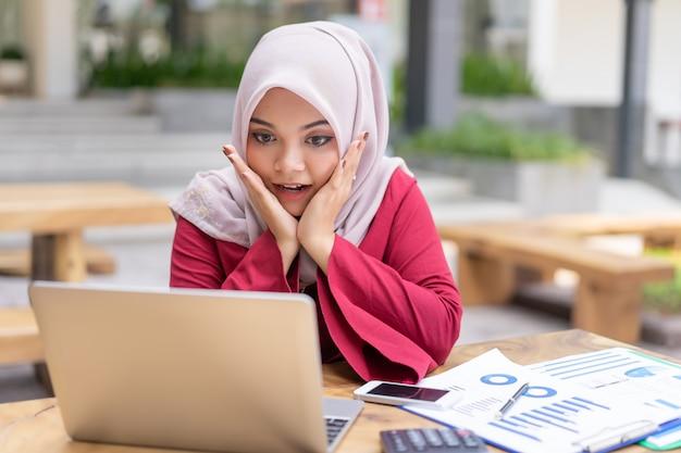 Glückliche moderne asiatische moslemische geschäftsfrau, die froh ist, hohe profite zu empfangen, hat eigenes wohlhabendes geschäft.