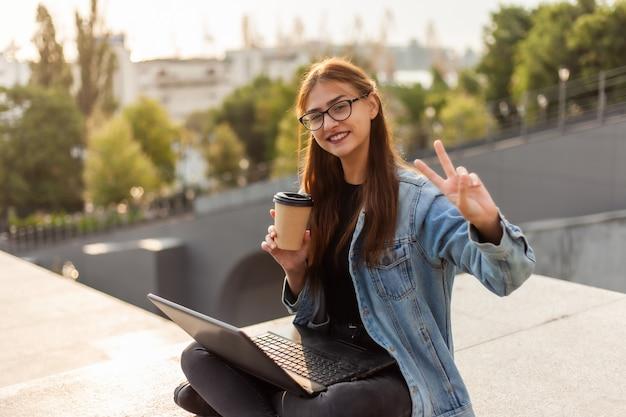 Glückliche moderne studentin in einer jeansjacke, die auf treppe mit laptop sitzt und eine geste v. fernunterricht zeigt. modernes jugendkonzept.