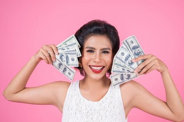 Glückliche modeschönheitshand, die dollargeld hält