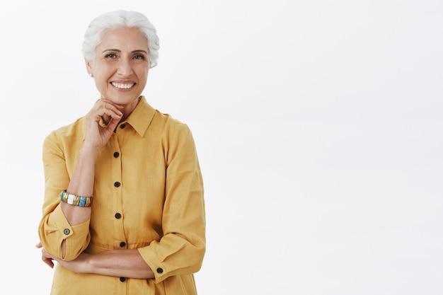 Glückliche modische ältere dame im gelben mantel, der fröhlich lächelt
