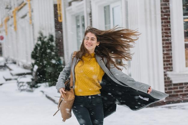 Glückliche modische junge frau, die schneefallwetter auf straße in der stadt genießt. langes brünettes haar, schneezeit, aufgeregte gefühle, die spaß haben, lächeln. weihnachtsstimmung, neues jahr, wahres glück.