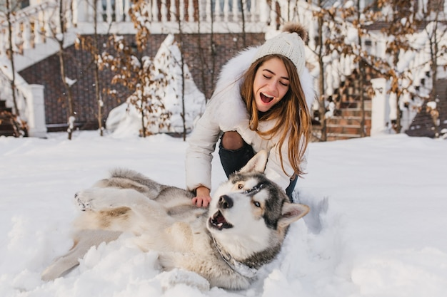 Glückliche momente auf winterzeit der erstaunlichen youful frau, die mit husky hund im schnee spielt. helle positive emotionen, wahre freundschaft, liebe zu haustieren, beste freunde, lächeln, spaß haben, winterferien.