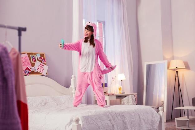 Glückliche momente. erfreutes schulmädchen, das einen weichen pyjama trägt und vor der kamera ein gesicht macht