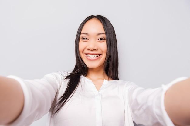 Glückliche momente müssen gespeichert werden. fröhliche junge asiatin, die kamera hält und selfie macht, während sie vor grauem hintergrund steht