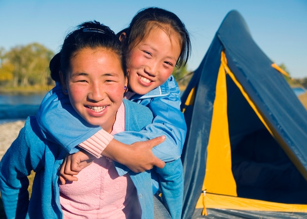 Glückliche mongolische mädchen, die piggyback am campingplatz spielen.