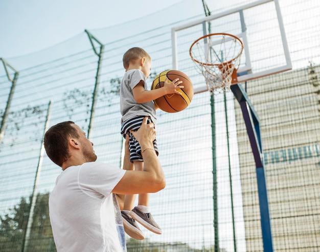 Glückliche monoparentale familie, die basketball spielt