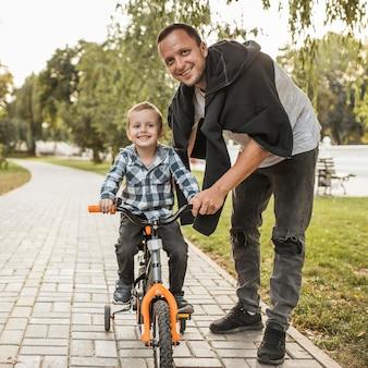 Glückliche monoparentale familie, die fahrrad fährt