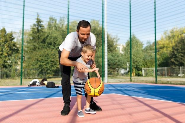 Glückliche monoparentale familie, die lernt, wie man basketball spielt