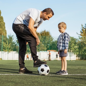Glückliche monoparentale familie, die lernt, wie man fußball spielt