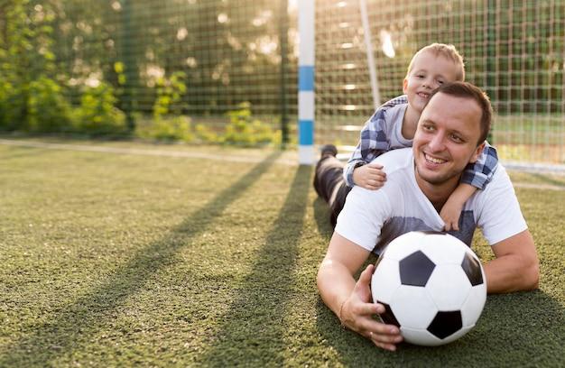 Glückliche monoparentale familie, die sich auf das gras stützt