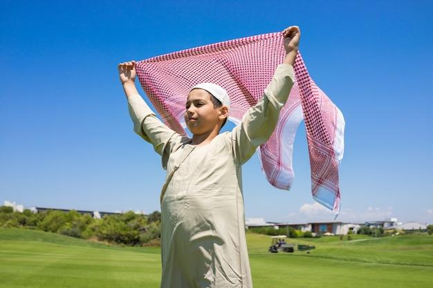 Glückliche moslemische familie auf wiese mit schal