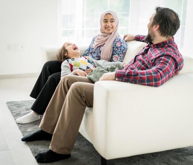 Glückliche moslemische familie, die zu hause auf sofa in lebendem roome sitzt