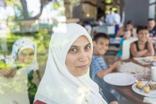 Glückliche moslemische familie im restaurant