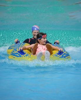 Glückliche moslemische familie, mutter und tochter im swimmingpool, sommerzeit-konzept